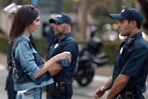 Kendall Jenner hands a can of Pepsi